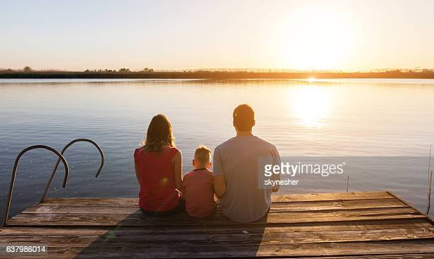 rear view of family at sunset relaxing by the river. - sunset lake stock photos and pictures
