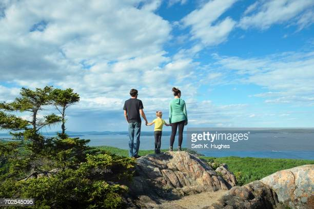 Rear view of family holding hands looking away at view of sea, Bar Harbor, Maine