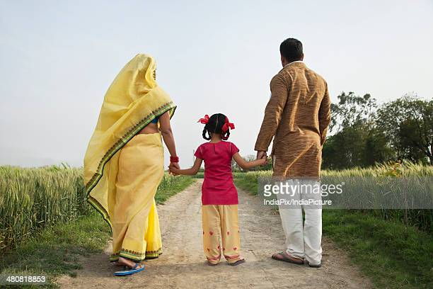 Rear view of family holding hands while walking in farm