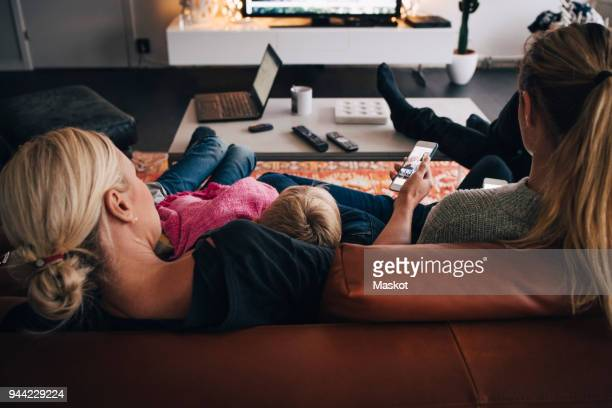 rear view of family sitting on sofa at home - family watching tv stock pictures, royalty-free photos & images