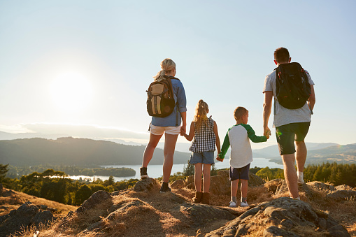 Rear View Of Family Standing At Top Of Hill On Hike Through Countryside In Lake District UK 1049858904