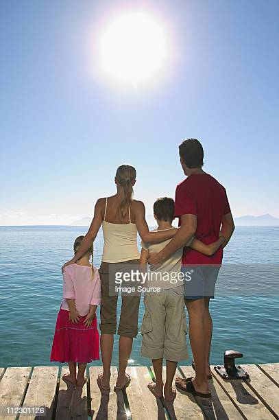 Rear view of family standing on jetty with sun shining