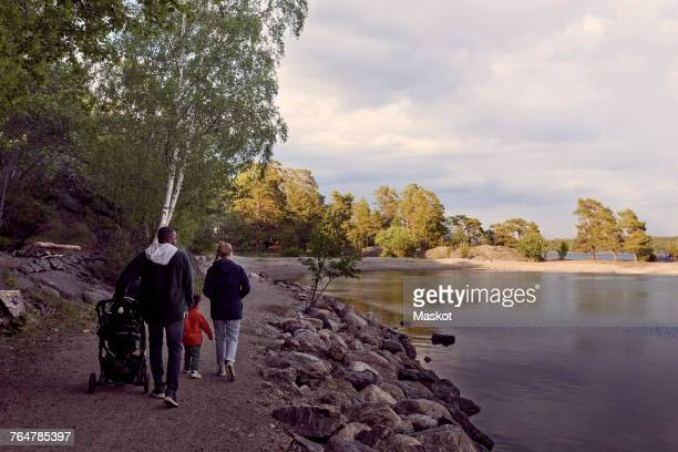 Rear view of family walking at lakeshore against sky