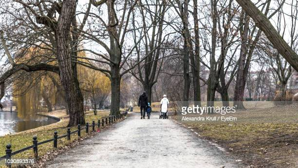 Rear View Of Family Walking At Park During Winter