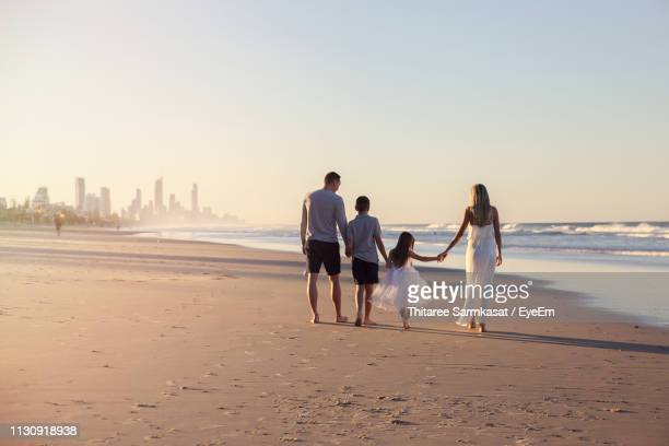 rear view of family walking on beach - gold coast queensland stock pictures, royalty-free photos & images