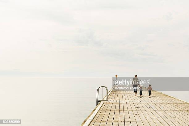 Rear view of family walking on pier at sea against sky