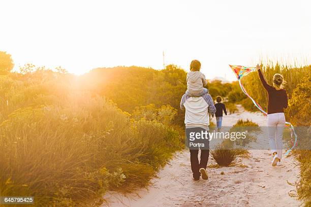 rear view of family walking on sandy footpath - candid beach stock photos and pictures