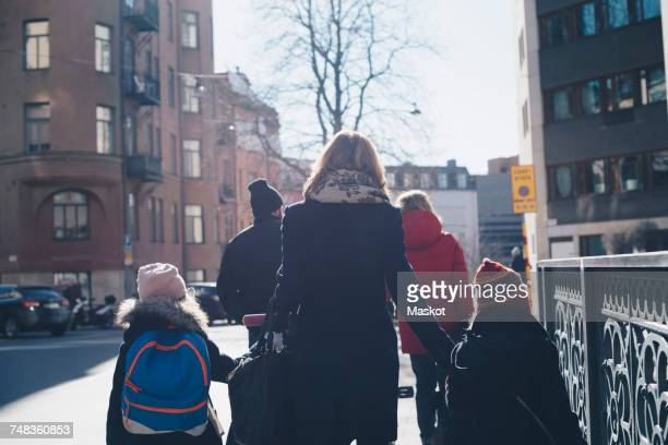 Rear view of family walking on sidewalk in city during sunny day