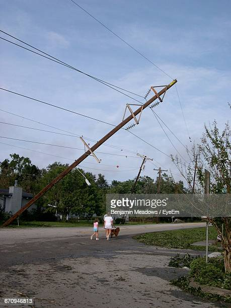 Rear View Of Family With Dog Walking On Street After Storm