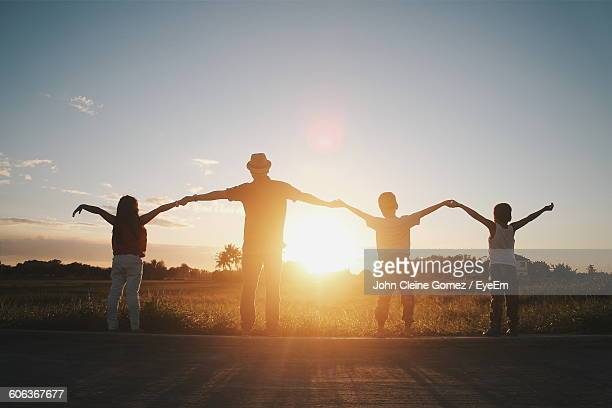 Rear View Of Family With Holding Hands While Arms Outstretched Against Sunset