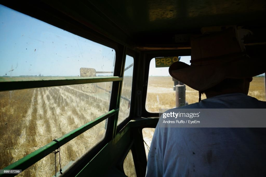 Rear View Of Farmer In Vehicle On Farm : Stock Photo