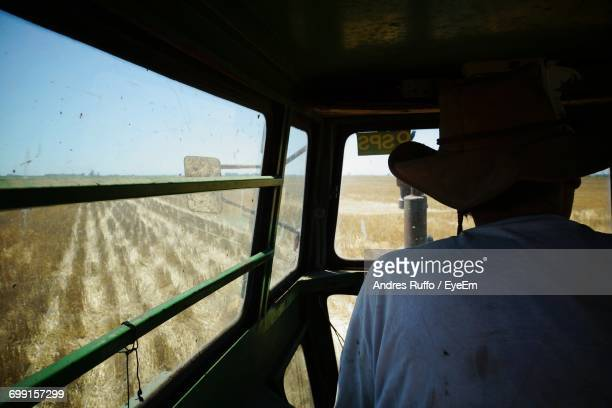 Rear View Of Farmer In Vehicle On Farm