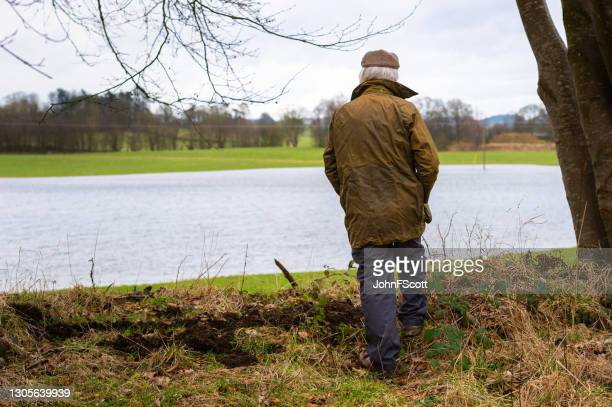 rear view of farmer looking at a flooded field - johnfscott stock pictures, royalty-free photos & images