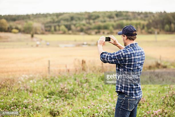 Rear view of farmer photographing field through mobile phone