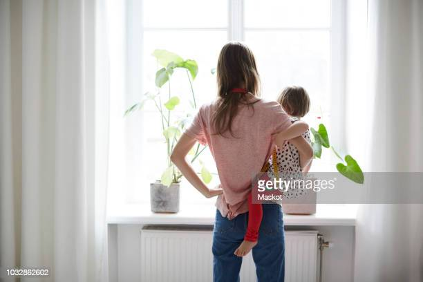 rear view of fashion designer carrying daughter while standing at home - homemaker stock pictures, royalty-free photos & images