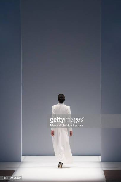 rear view of fashion model walking on ramp - catwalk stock pictures, royalty-free photos & images