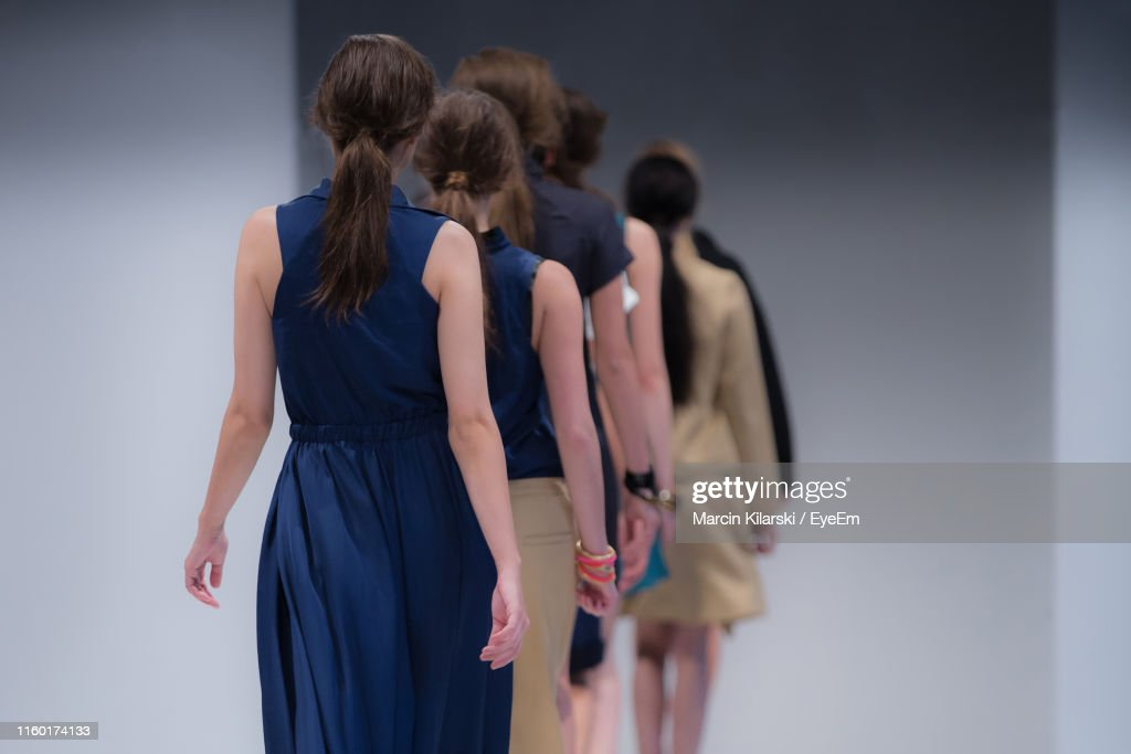 Rear View Of Fashion Models Walking In Row On Stage : Stock Photo