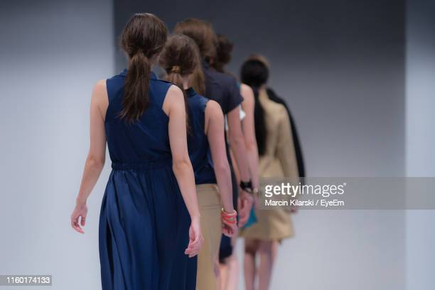 rear view of fashion models walking in row on stage - desfile de moda imagens e fotografias de stock