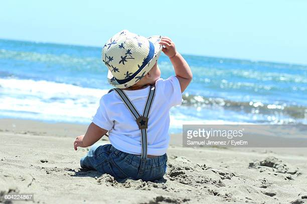 rear view of fashionable baby in hat sitting on sea shore - サスペンダー ストックフォトと画像