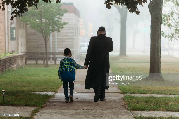 rear view of father and boy walking on footpath during foggy weather - judaism stock pictures, royalty-free photos & images