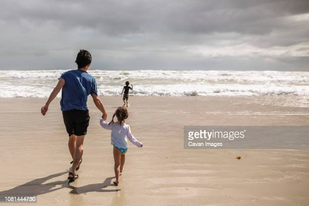 rear view of father and daughter holding hands while son running towards sea on shore at beach - swimwear stock pictures, royalty-free photos & images