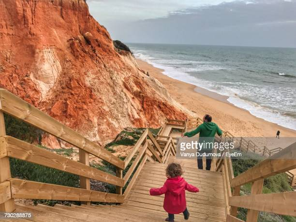 rear view of father and daughter moving down on wooden steps at beach - albufeira stock pictures, royalty-free photos & images