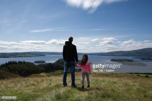 Rear View Of Father And Daughter Standing On Grassy Field Against Sky