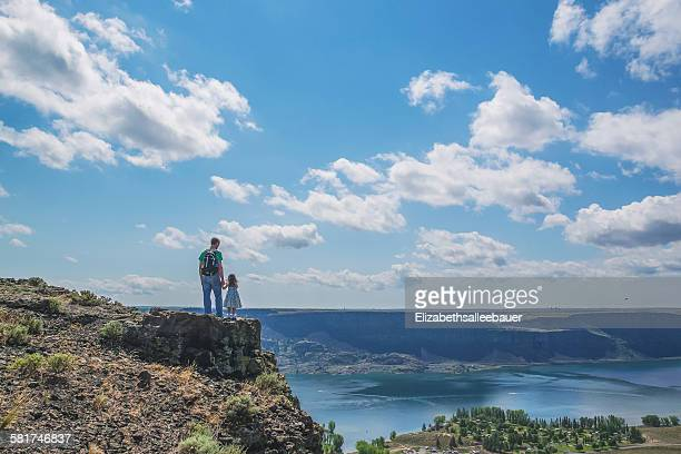 Rear view of father and daughter standing on top of a mountain