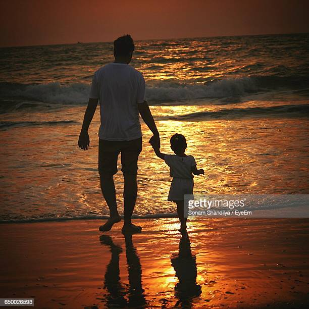 Rear View Of Father And Daughter Walking At Beach During Sunset