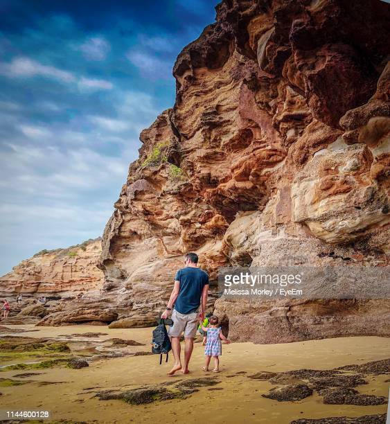 rear view of father and daughter walking by rock formations - newcastle new south wales stock pictures, royalty-free photos & images