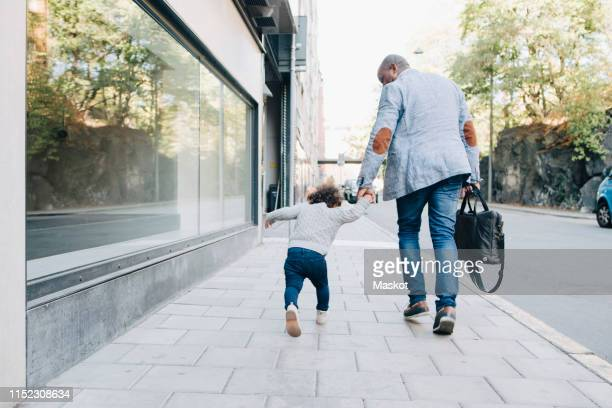 rear view of father and daughter walking on sidewalk in city - day 2 stock-fotos und bilder