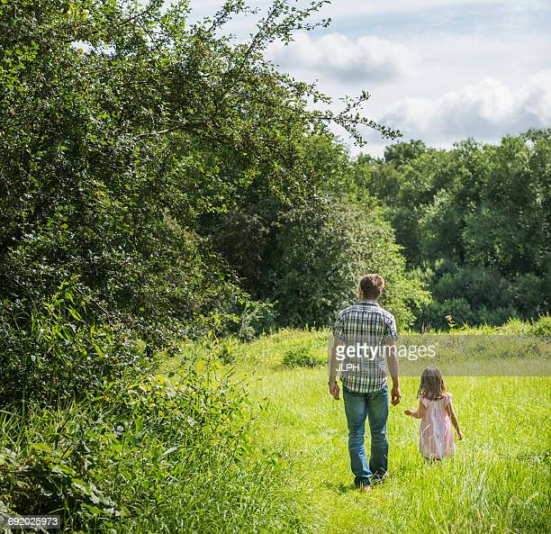 Rear view of father and daughter walking through meadow, Porta Westfalica, North Rhine Westphalia, Germany