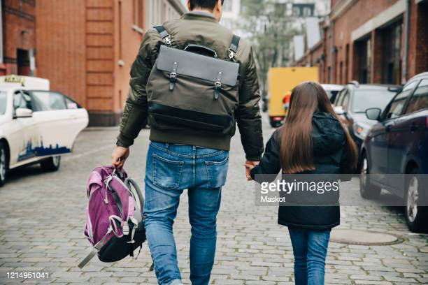 rear view of father and daughter with backpack walking on footpath in city - familie mit einem kind stock-fotos und bilder