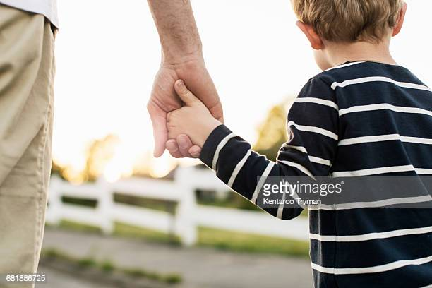rear view of father and son holding hands while standing outdoors - sohn stock-fotos und bilder