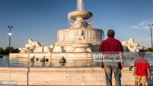 Rear View Of Father And Son Standing Against Fountain