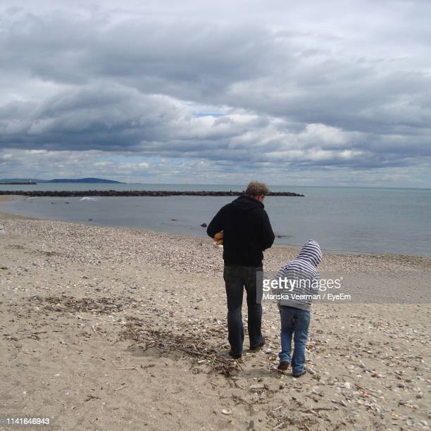 rear view of father and son standing at beach against sky - herault stock pictures, royalty-free photos & images