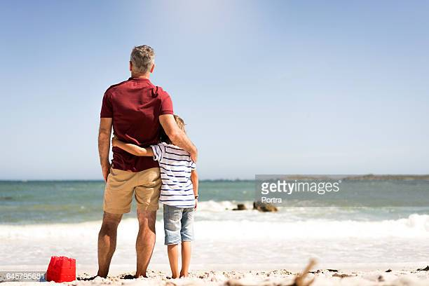 Rear view of father and son standing on shore