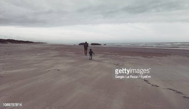 rear view of father and son walking at beach against sky - son la stock pictures, royalty-free photos & images