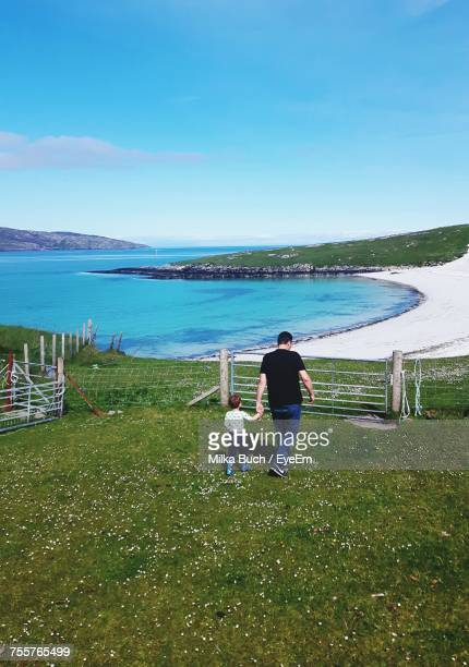 Rear View Of Father And Son Walking On Hill By Sea Against Blue Sky During Sunny Day