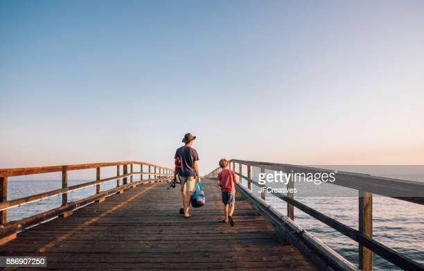 rear view of father and son walking on pier, goleta, california, united states, north america - pier stock pictures, royalty-free photos & images