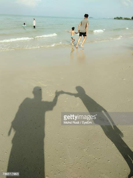 Rear View Of Father And Son Walking On Shore At Beach