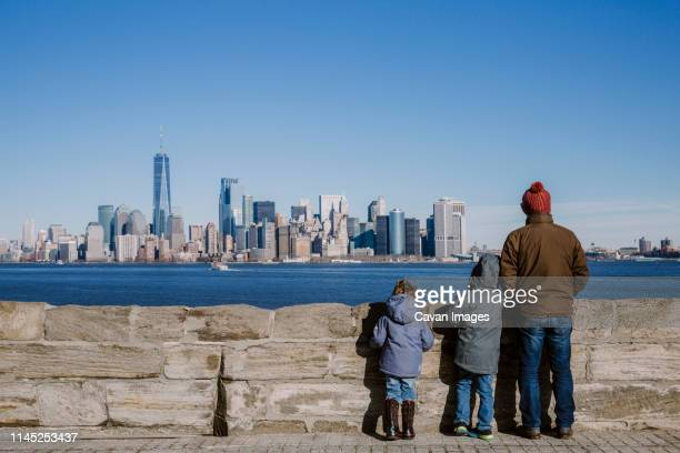 rear view of father and sons wearing warm clothing looking at cityscape by river against sky - nordamerika stock-fotos und bilder
