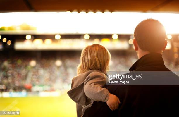 rear view of father carrying daughter at soccer stadium - carinhoso imagens e fotografias de stock