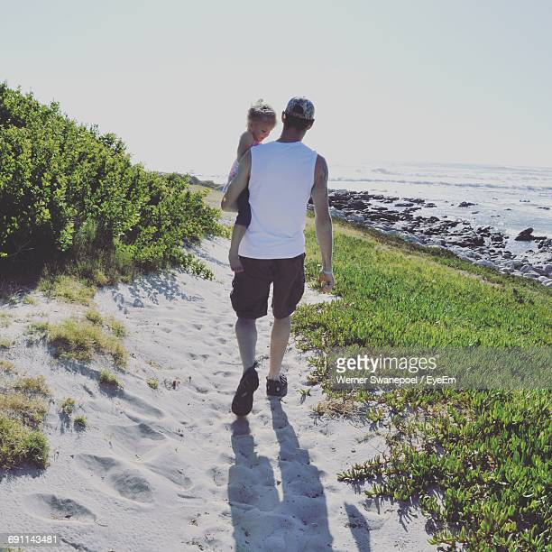 rear view of father carrying daughter while walking at beach against clear sky - débardeur photos et images de collection