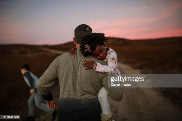 Rear view of father carrying daughter while walking on dirt road during sunset