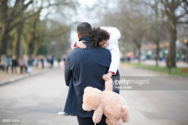 Rear view of father carrying sleeping daughter holding cuddly toy