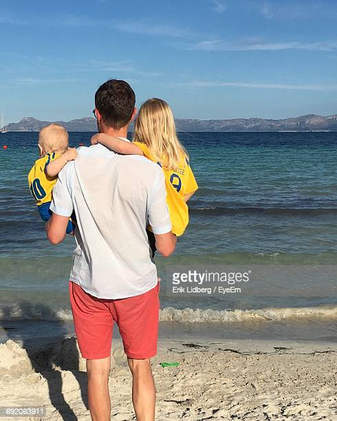 Rear View Of Father Carrying Son And Daughter On Shore At Beach Against Sky
