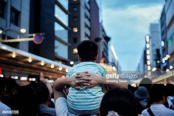Rear View Of Father Carrying Son On Shoulders On Street At Dusk