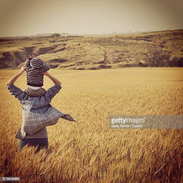 Rear View Of Father Carrying Son On Shoulders On Wheat Field Against Sky