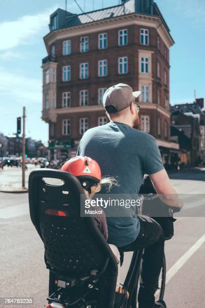 Rear view of father cycling while daughter sitting on back seat in city